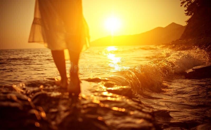 Beine einer Frau durch das Meer auf dem Strand lizenzfreie stockbilder