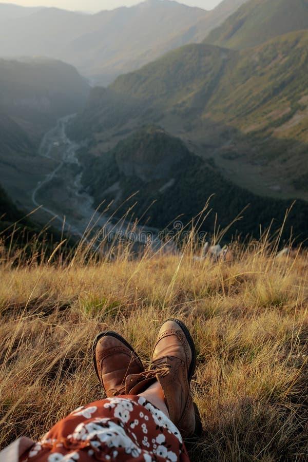 Beine eines Mädchens in den Stiefeln vor dem hintergrund der Berge lizenzfreie stockbilder