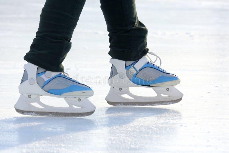 Beine eines Mannes, der auf die Eisbahn eisläuft lizenzfreie stockfotos