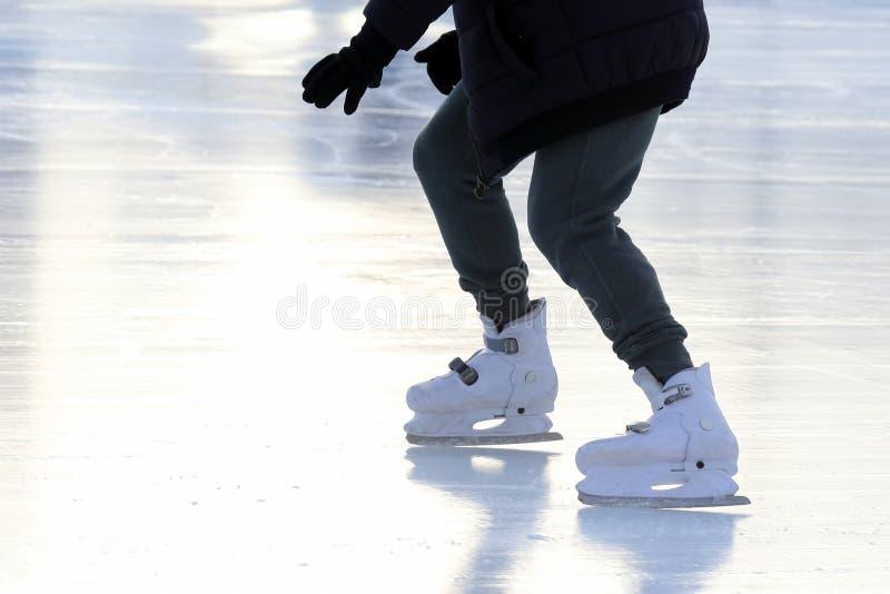 Beine eines Mannes, der auf die Eisbahn eisläuft stockfoto