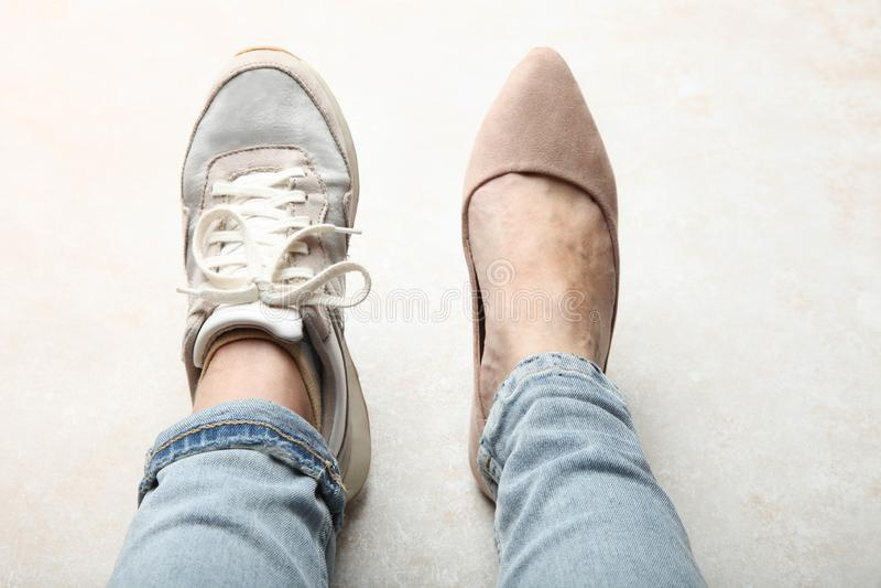 Beine im Sportschuh und in den schönen eleganten klassischen Schuhen lizenzfreie stockbilder