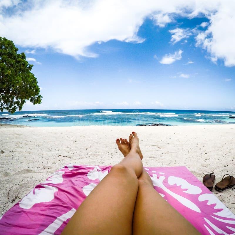 Beine mit gefälschtem Spray bräunen sich auf Sonnenruhesessel auf tropischem Strand mit p lizenzfreie stockfotografie