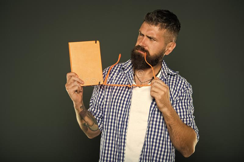 Being absorbed in thinking. University male student holding lecture notes. Bearded man with party glasses and lesson stock photos