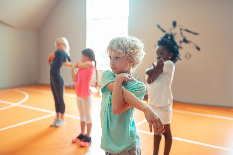 Concentrated school children at their sports lesson. Being attentive. Four concentrated children training and listen to the coach at their sports lesson royalty free stock photos