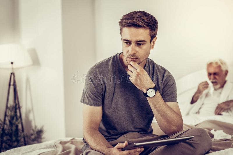 Upset son thinking about the diagnosis of his coughing dad. Being concerned about medical diagnosis. Upset concerned son thinking about the medical diagnosis of royalty free stock photos