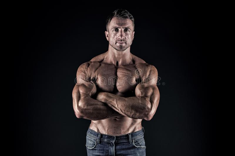 Being enthusiastic for sports. Sportsman or sport man keeping strong arms crossed. Sexy fit man with athletic torso on stock photography