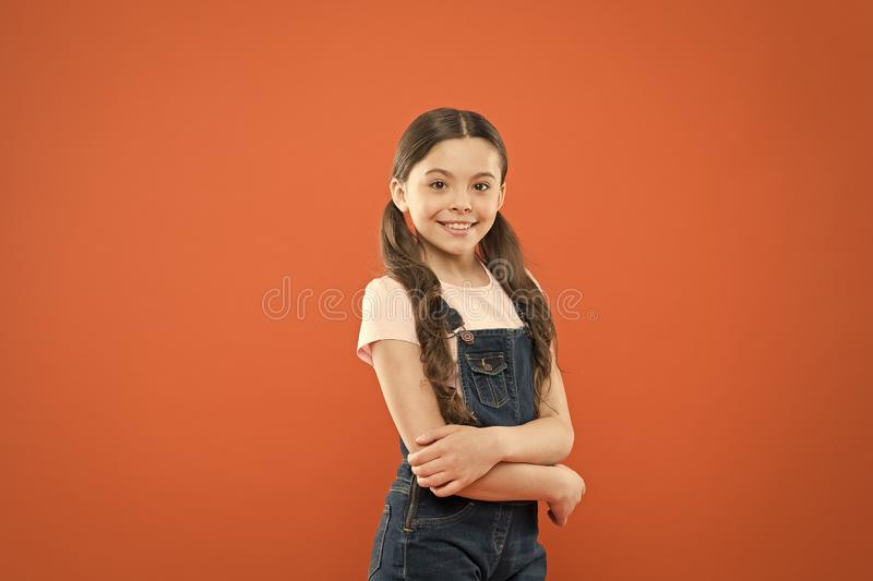 Being great every day. Fashion baby girl. Cute little fashion model on orange background. Small child with fashion look. Adorable kid with long brunette hair royalty free stock photos