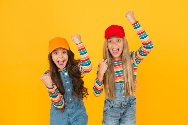 Being happy and victorious. Little girls making victory gestures on yellow background. Cute small winners enjoying stock photo