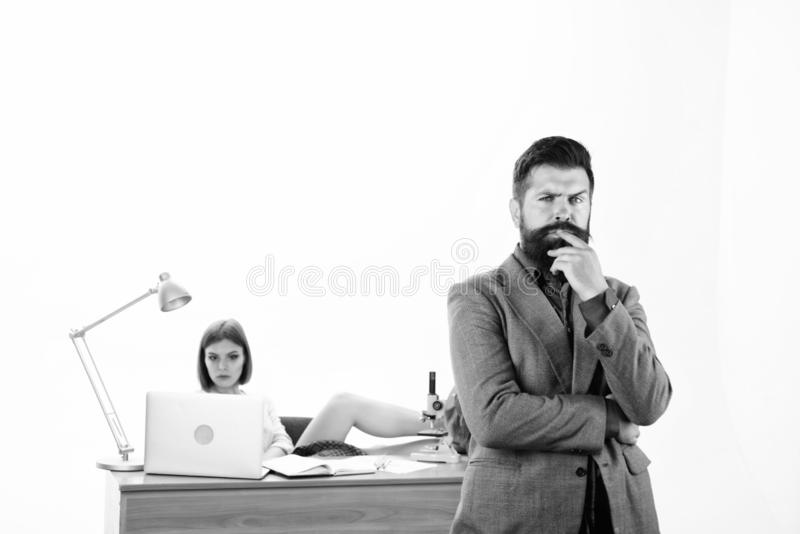 Being his own boss. Boss and subordinate. Serious boss and female coworker in office. Bearded boss with pretty employee. Working in background royalty free stock image