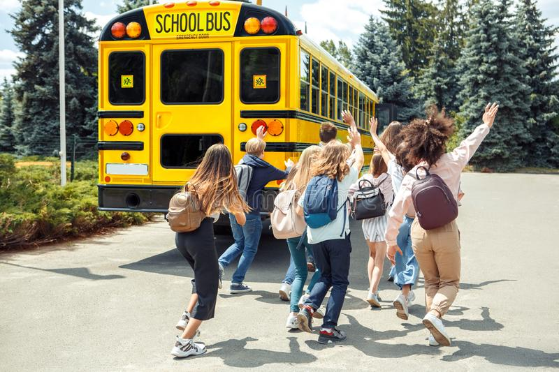 Being late. Classmates running to school bus back view waving to driver. Group of children classmates running to school bus being late back view waving to driver royalty free stock photos