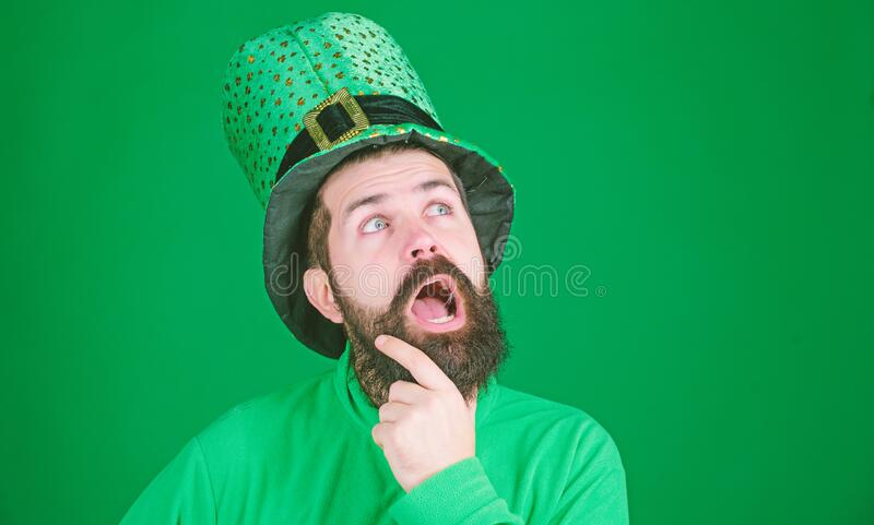 Being lost in contemplation. Hipster keeping mouth open in leprechaun hat and costume. Bearded man celebrating saint royalty free stock image
