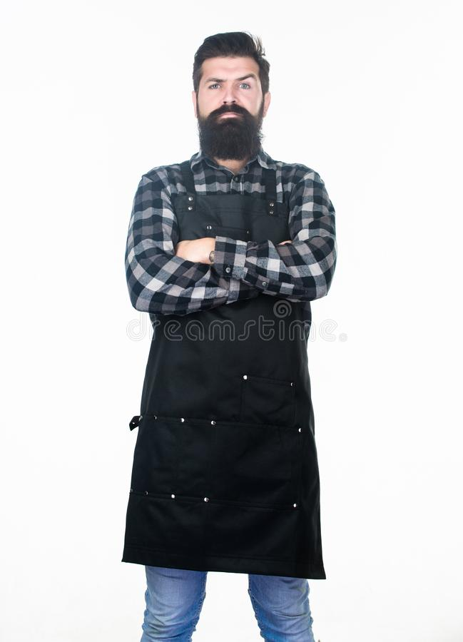 Being lost in serious thought. Bearded man with serious look wearing work apron. Hipster with long beard and mustache on. Serious face. Serious man keeping arms royalty free stock image