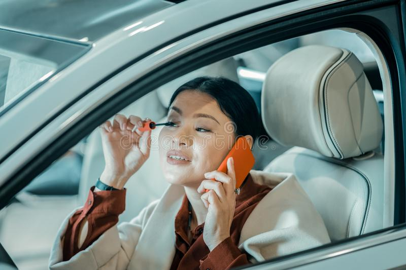 Busy woman putting on maskara on drivers seat. Being multitasking. Busy beautiful woman putting maskara on her eyelashes sitting on drivers seat of her car stock photo