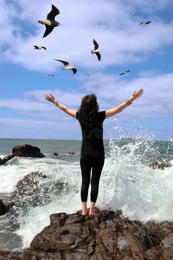 Being at one with all of nature. A beautiful woman on the edge of the rocks with waves splashing and seagulls flying being happy and relaxed in nature stock photography