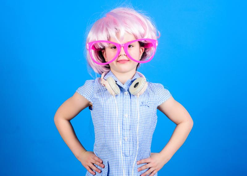 Being a party child. Small child wearing hair wig and fancy glasses with headphones. Adorable child enjoy listening to. Music. Cute little child with party look royalty free stock image