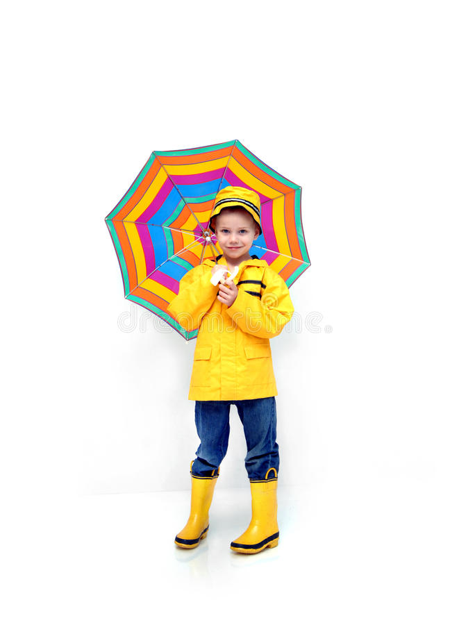 Being Prepared. Little boy stands prepared for rain. He is wearing a yellow raincoat and hat. He is carrying a striped umbrella and has his jeans tucked into stock photography