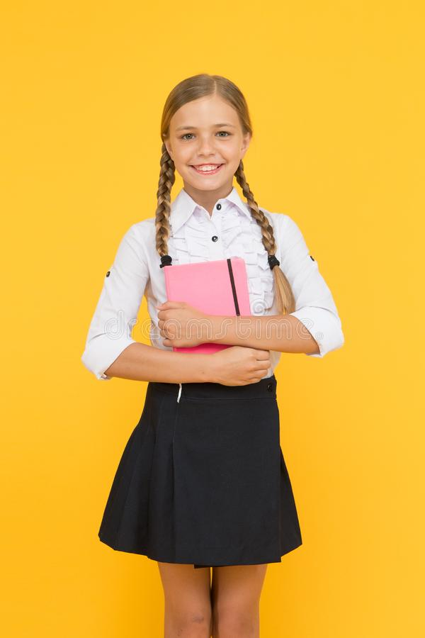 Being proud of her knowledge. Cute little child with school knowledge in hands. Adorable small girl holding book on royalty free stock photo