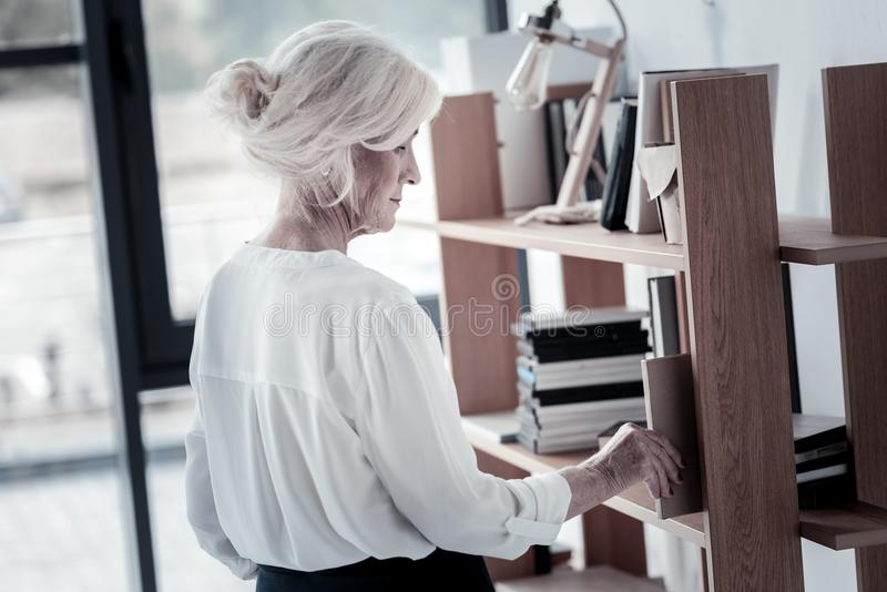 Serious woman taking necessary folder. Being ready. Concentrated blonde bowing head and looking downwards while standing in semi position stock photos