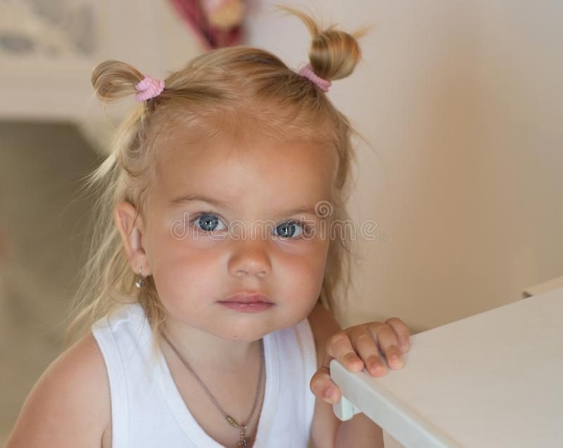 Being a real cutie. Small girl with bun ponytails. Small child wear funny hairstyle. Adorable child with blond hair stock image