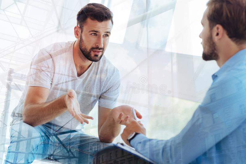 Handsome bearded man explaining his problem to psychiatrist. Being sincere. Waist up of young bearded men waving hands and explaining his problem to psychiatrist stock images
