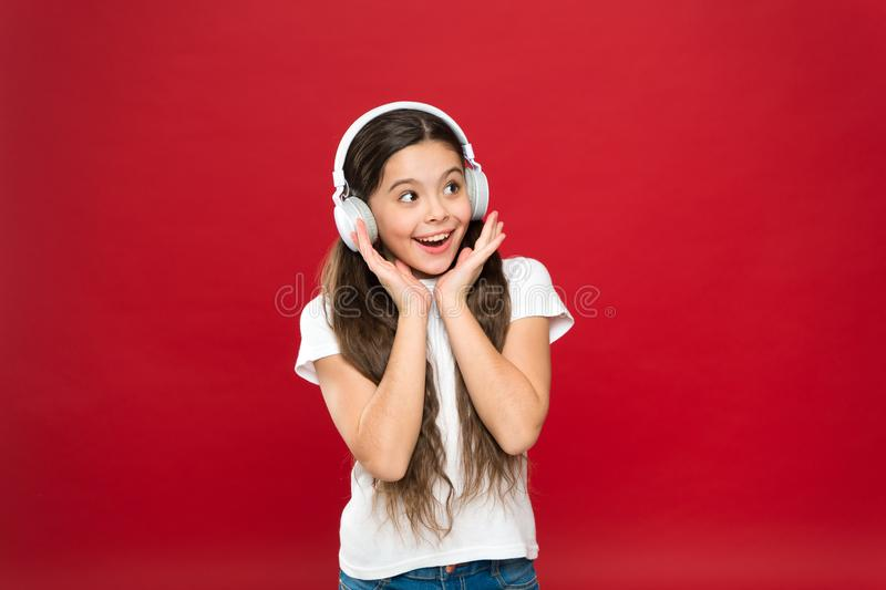 Being too excited with her cool gadget. Little girl listening to music. Small girl wearing headphones. Cute music fan stock photography
