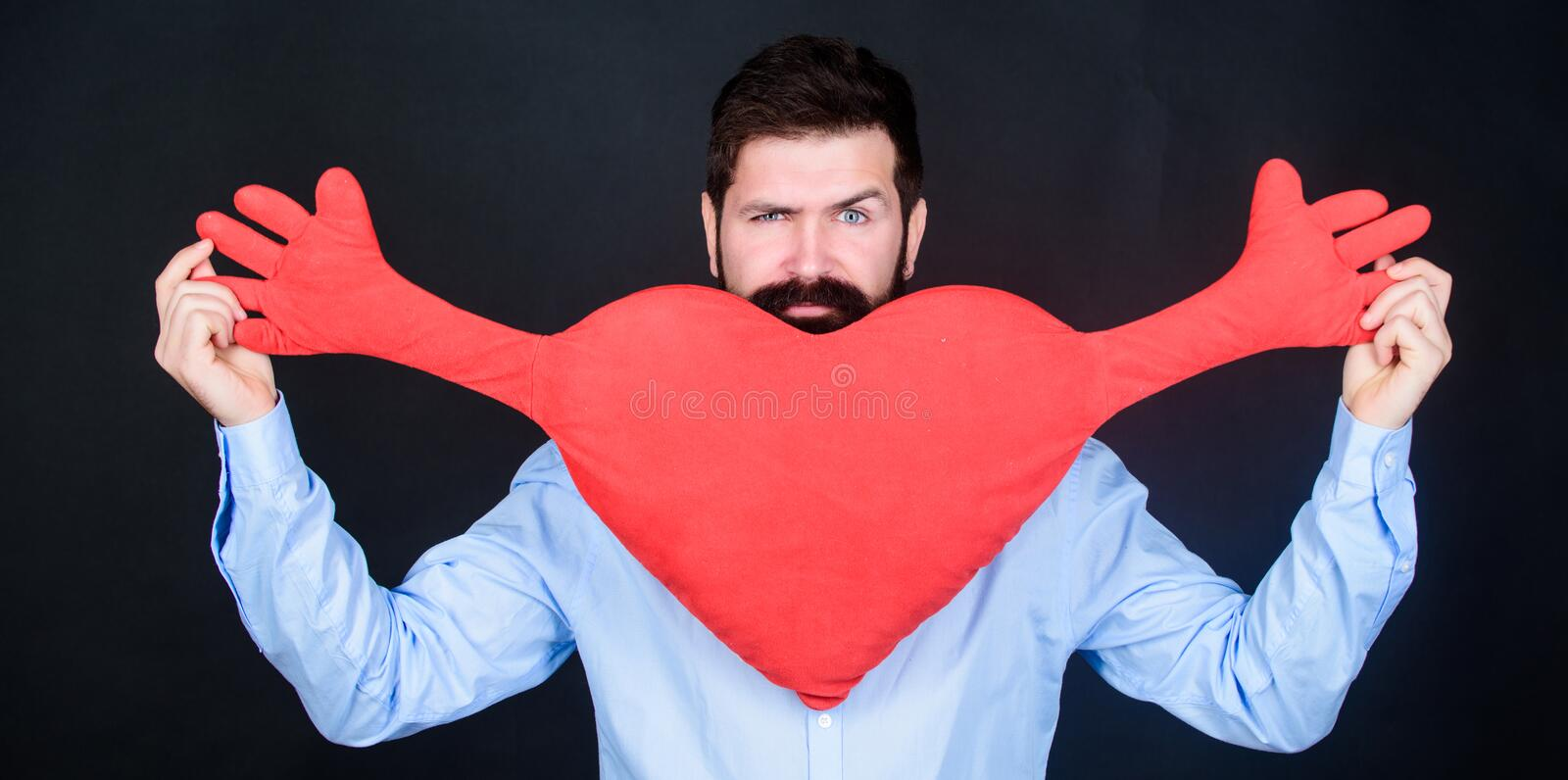 Being utterly romantically lovestruck. Having heart attack and heartache. Unhealthy man holding big red heart. Valentines man expressing love on 14 february royalty free stock photos