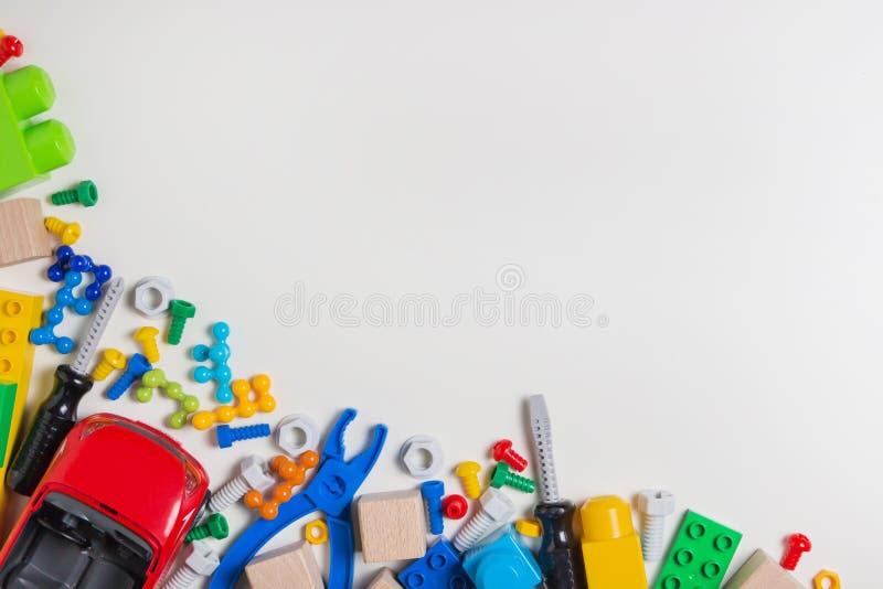 Beira colorida dos brinquedos das crianças Brinque ferramentas, blocos da construção, cubos no fundo branco como o quadro Configu imagem de stock