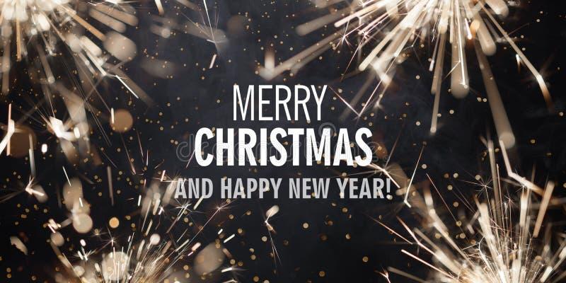 Beira com chuveirinhos ardentes e Feliz Natal do texto e ano novo feliz foto de stock royalty free