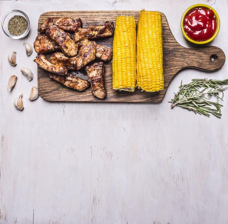 A beira com os reforços fritados deliciosos do cordeiro em uma placa de corte grelhou com molho picante, ervas e milho com área d imagens de stock royalty free