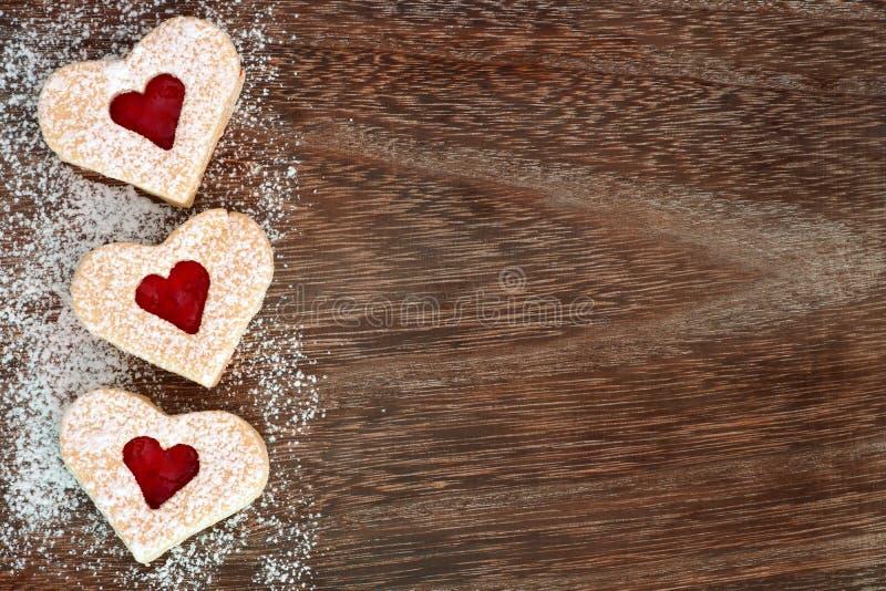 Beira das cookies do coração do dia de Valentim com açúcar pulverizado sobre a madeira fotografia de stock