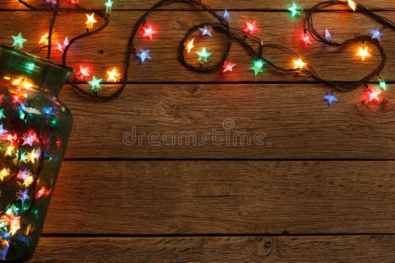Beira das luzes de Natal no fundo de madeira fotos de stock royalty free