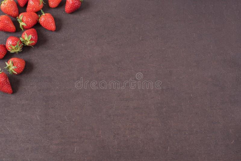 A beira de morangos vermelhas maduras frescas inteiras arranjou em lados esquerdos em um fundo textured escuro da ardósia com cop imagens de stock
