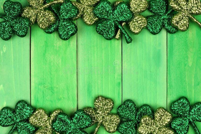 Beira do dobro do dia do St Patricks dos trevos sobre a madeira verde fotografia de stock royalty free
