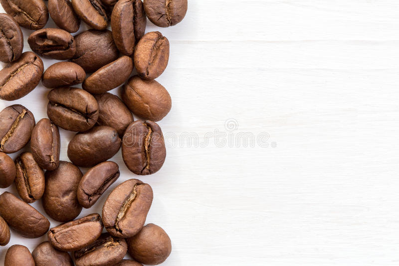 Beira do feijão de café na superfície da madeira imagens de stock