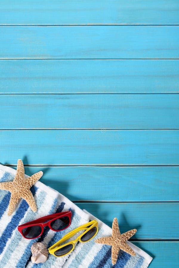 Beira do fundo da praia do verão, óculos de sol, toalha, estrela do mar, espaço de madeira azul da cópia, vertical imagem de stock royalty free