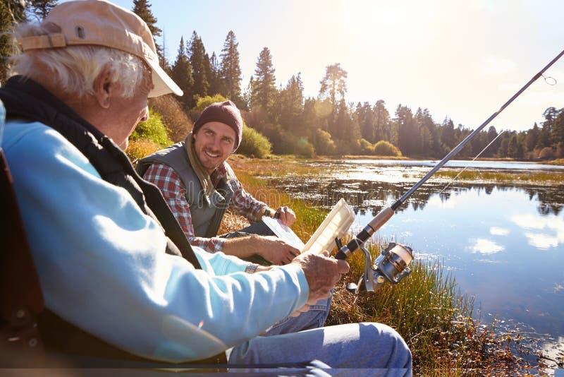 Beira do lago da pesca do filho do pai e do adulto, close-up imagem de stock royalty free