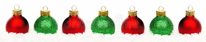 Beira do Natal de quinquilharias vermelhas e verdes na neve isolada fotos de stock royalty free
