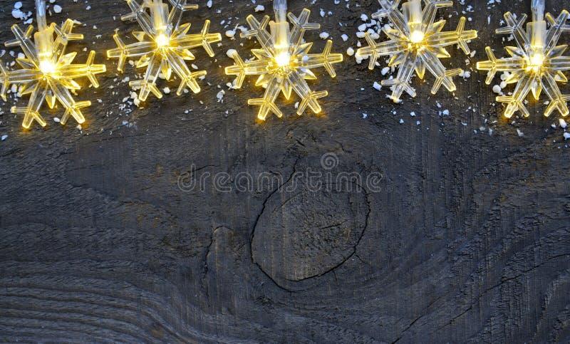 Beira do Natal A festão dos flocos de neve ilumina-se no fundo rústico de madeira velho Fundo do Natal Feriados de inverno, Feliz fotos de stock
