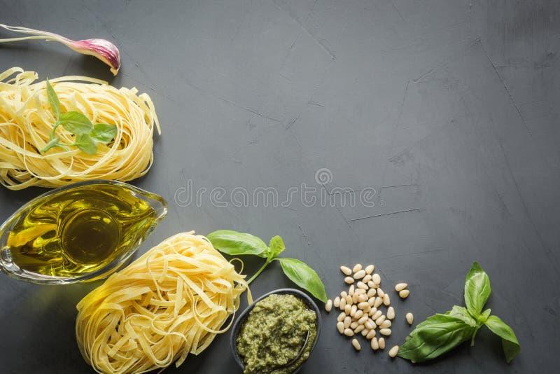 Beira do trigo de trigo duro cru da massa, pesto, manjericão, Parmesão para cozinhar pratos mediterrâneos Vista superior, espaço  imagens de stock