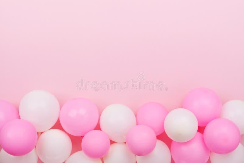 Beira dos balões coloridos para o aniversário na opinião de tampo da mesa do rosa pastel estilo liso da configuração fotografia de stock