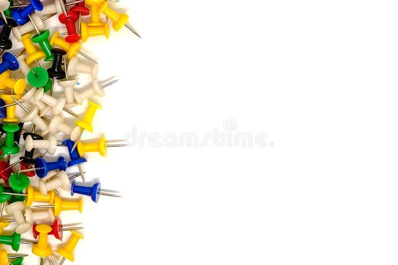 Beira esquerda de multicolour dos pinos do impulso no fundo branco foto de stock royalty free