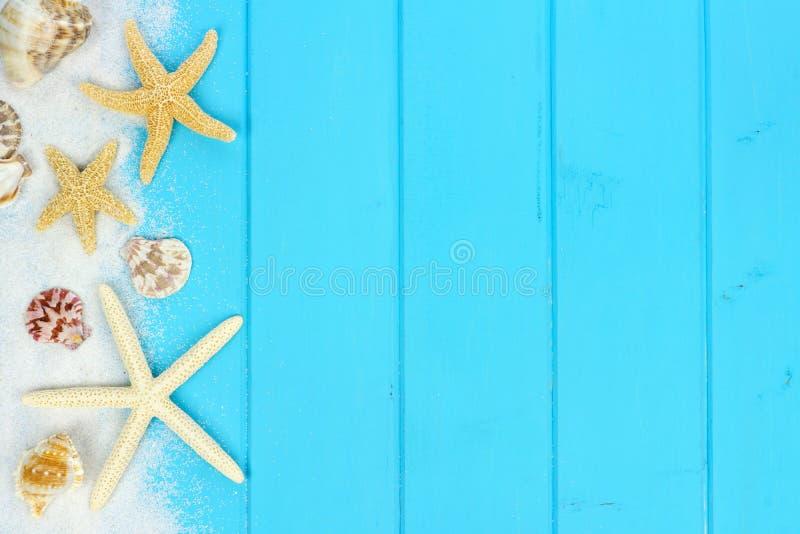 Beira lateral da areia, das conchas do mar e da estrela do mar na madeira azul imagem de stock