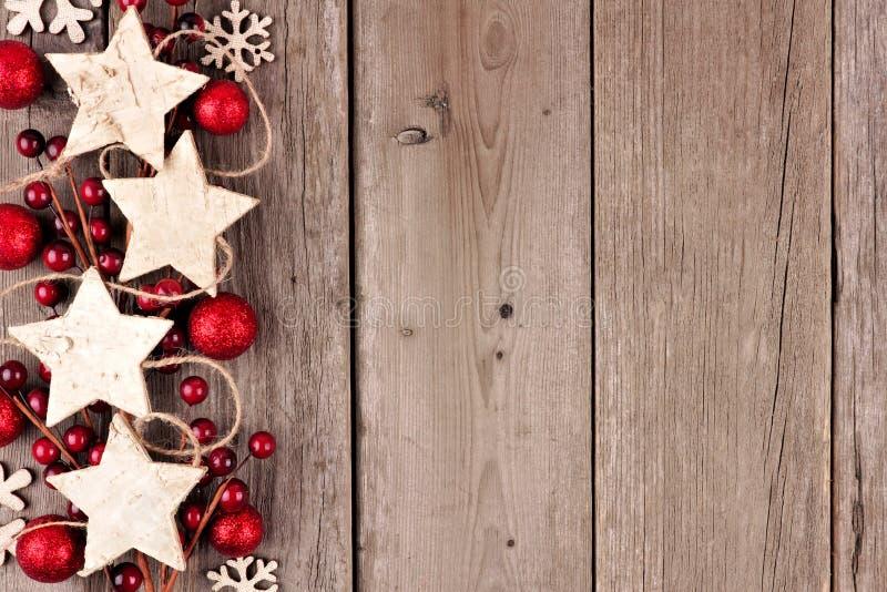 Beira lateral do Natal com os ornamento e as quinquilharias de madeira rústicos da estrela na madeira envelhecida foto de stock