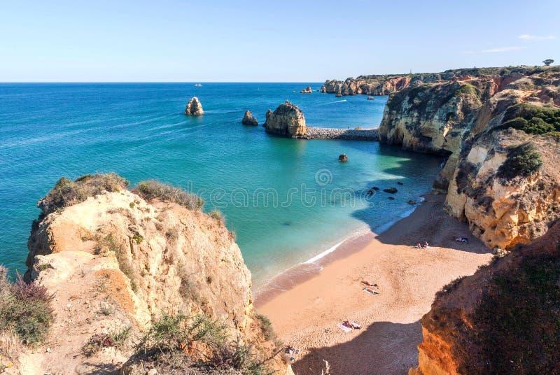 Beira-mar sob o nivelamento do sol em Portugal Paisagem portuguesa com ondas de oceano e alguns turistas na praia imagem de stock royalty free