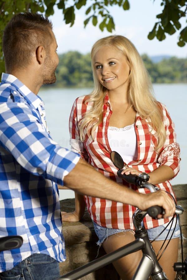 Beira-rio louro feliz do homem da reunião da mulher exterior imagens de stock