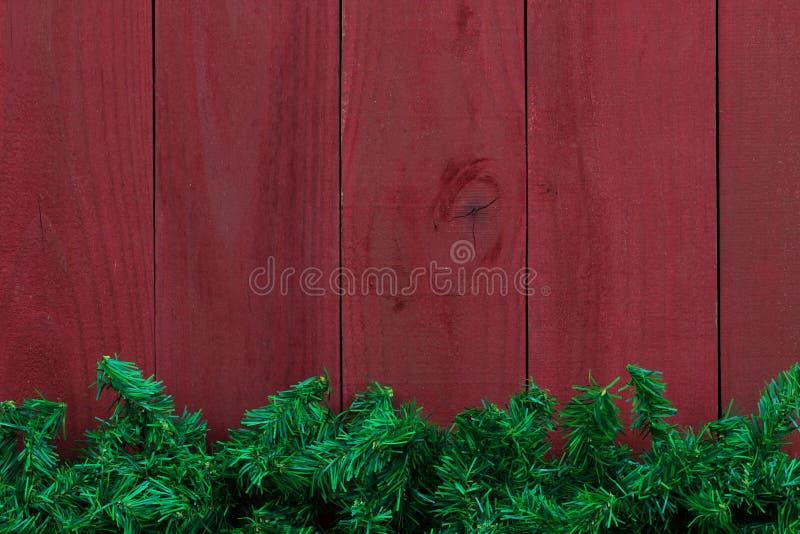 Beira sempre-verde da festão da árvore do Natal com fundo de madeira vermelho antigo foto de stock