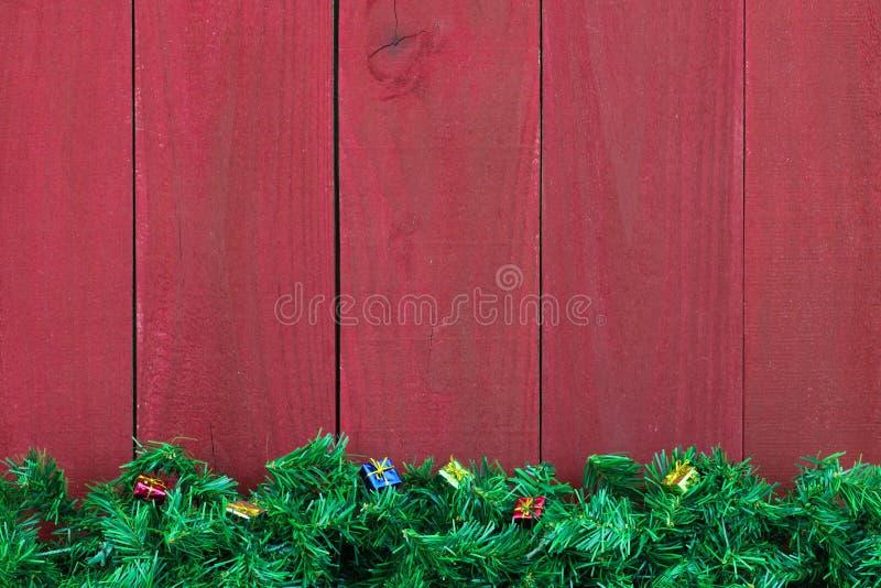 Beira sempre-verde da festão da árvore do Natal com presentes pelo fundo de madeira vermelho antigo imagens de stock