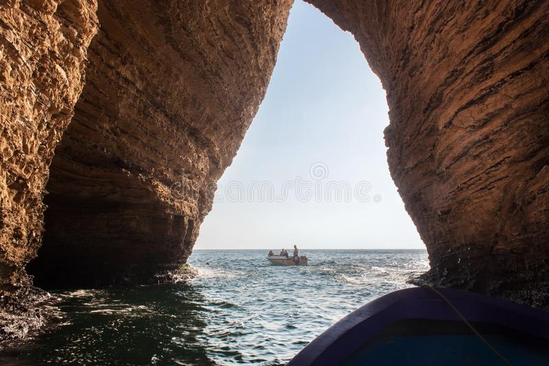 BEIROET, LIBANON - AUGUSTUS 14, 2014: Motorboot in Middellandse Zee met onbekende toeristen onder de boog van de beroemde Duifrot royalty-vrije stock afbeeldingen