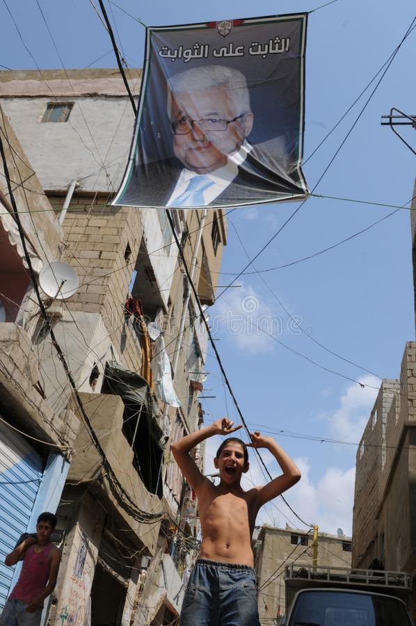 Beirut: Boy underneath political leader poster in shatila royalty free stock photography