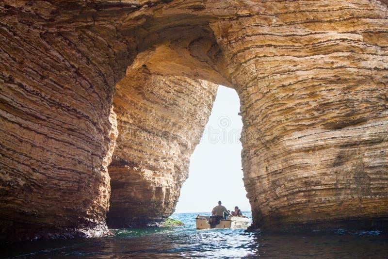 BEIRUT, L?BANO - 14 DE AGOSTO DE 2014: Motora en el mar Mediterr?neo con los turistas desconocidos debajo del arco de las rocas f fotografía de archivo libre de regalías